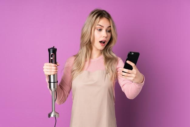 Menina russa adolescente usando um liquidificador isolado em um fundo roxo, segurando um café para levar e um celular