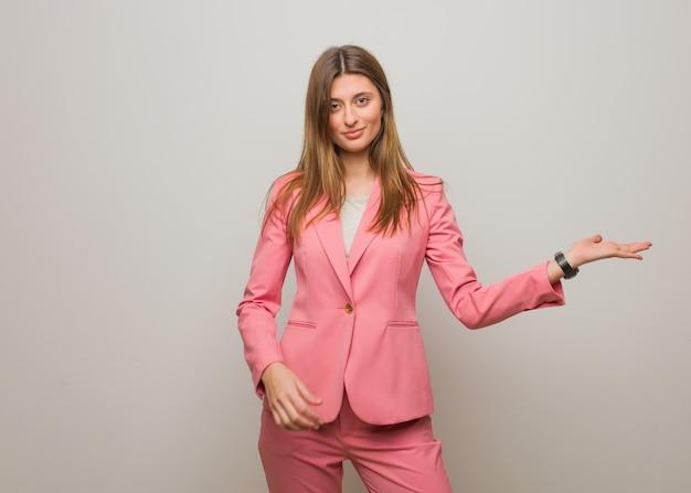 Menina russa de negócios jovem segurando algo com a mão