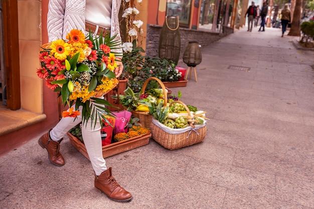 Menina saindo de uma floricultura com um buquê de flores