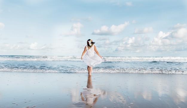 Menina saindo do mar vestindo roupas brancas