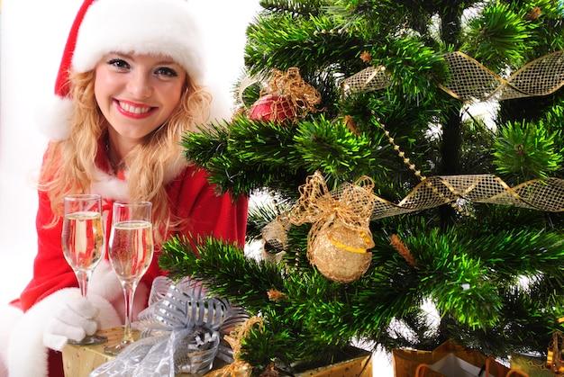 Menina santa de natal com presentes e taças de champanhe.