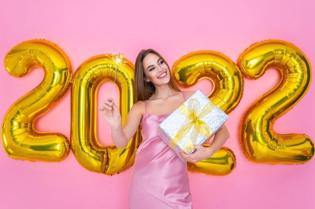 Menina santa sorridente e feliz segurando uma caixa de brilho e presente em balões de ar nas mãos, ano novo