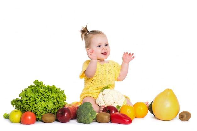 Menina são cercam de legumes e frutas, isoladas sobre o branco