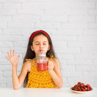 Menina satisfeita bebendo smoothies de morango em jar