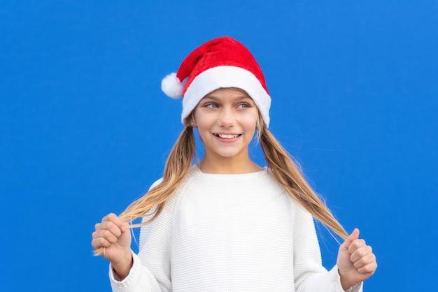 Menina satisfeita com um suéter branco e um chapéu de papai noel segurando rabo de cavalo sorrindo e isolado