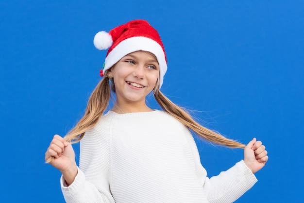 Menina satisfeita com um suéter branco e um chapéu de papai noel segurando tranças e sorrindo isolado