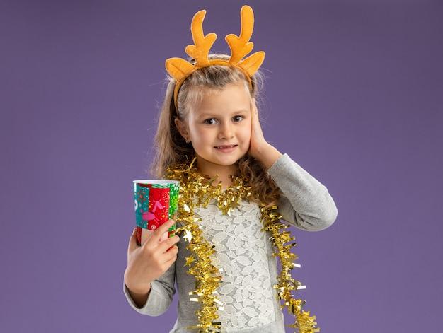 Menina satisfeita com uma argola de cabelo de natal com guirlanda no pescoço, segurando o copo de natal, colocando a mão na bochecha isolada em um fundo azul com espaço de cópia