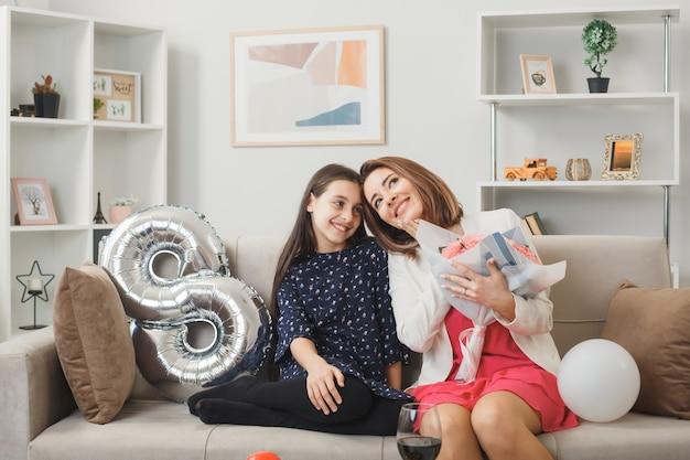 Menina satisfeita e mather com buquê no dia da mulher feliz sentada no sofá na sala de estar