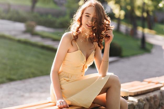 Menina satisfeita em um lindo vestido de verão brincando com seu cabelo ruivo. foto ao ar livre de uma jovem encantadora, aproveitando o fim de semana ensolarado quente.