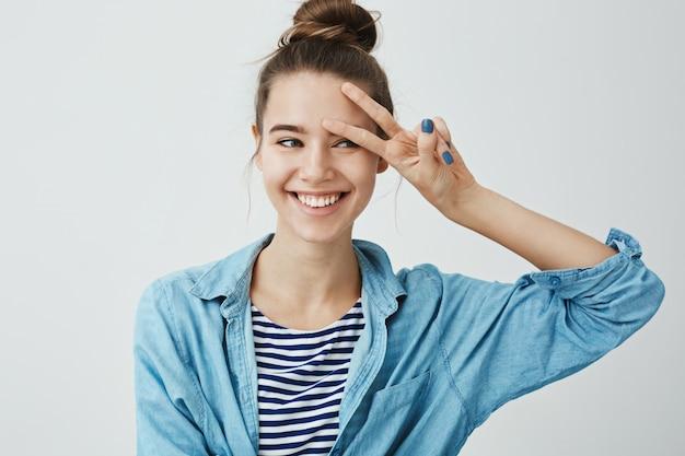 Menina saúda o bonitão na festa. foto interior de uma jovem encantadora positiva mostrando sinal de v na testa, olhando de lado e sorrindo amplamente, tentando impressionar ou seduzir alguém