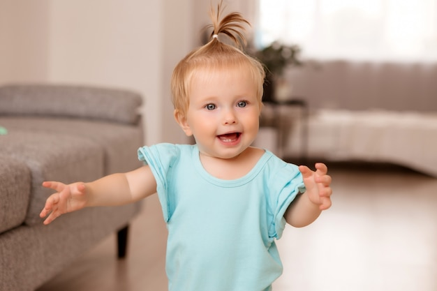 Menina saudável em uma sala ao lado de um sofá cinza está aprendendo a andar