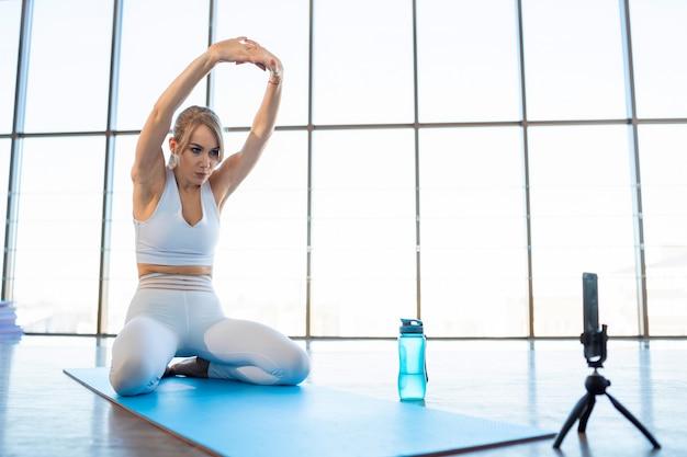 Menina se aquecendo enquanto está sentada na esteira de ioga na frente da câmera do telefone