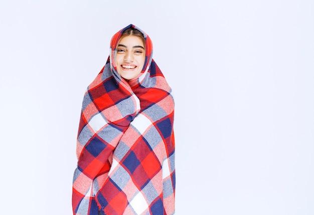 Menina se cobrindo com um cobertor azul vermelho, pois está sentindo frio.