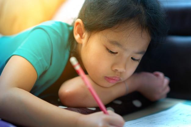Menina se deita para escrever o caderno no chão