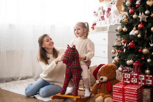 Menina se divertindo com a mãe em casa perto de árvore de natal