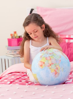 Menina se divertindo com um globo terrestre