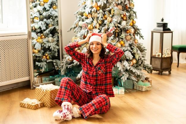 Menina se divertindo e comemorando o natal. no fundo decorou a árvore de natal com presentes.