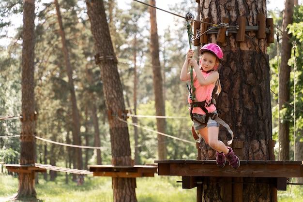 Menina se divertindo em um parque de aventura Foto gratuita