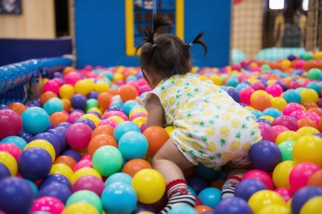 Menina se divertindo na piscina de bolas