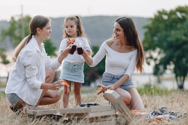 Menina se divertindo no piquenique, pizza, bebidas, verão e gramado