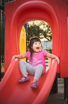 Menina se divertindo para jogar slider no recreio no horário de verão