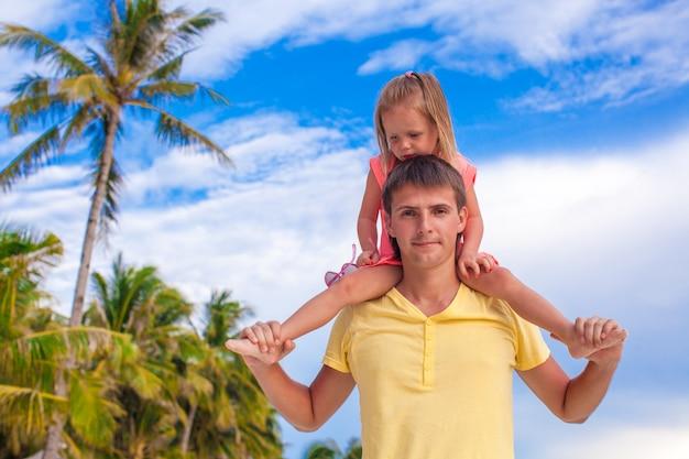 Menina se divertir com o pai na praia tropical