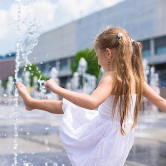 Menina se divertir na fonte de rua aberta no dia quente de verão