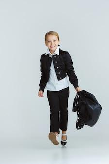 Menina se preparando para a escola depois de uma longa pausa de verão. de volta à escola. modelo feminino caucasiano posando com uniforme da escola com mochila na parede branca. infância, educação, conceito de férias.