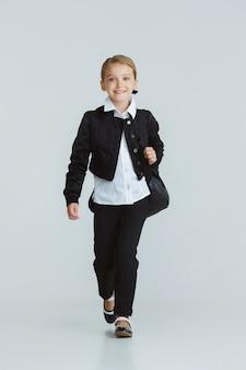 Menina se preparando para a escola depois de uma longa pausa de verão. de volta à escola. modelo feminino caucasiano posando com uniforme da escola na parede branca. infância, educação, conceito de férias.