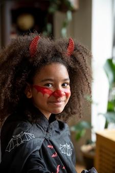 Menina se preparando para o halloween com uma fantasia de demônio