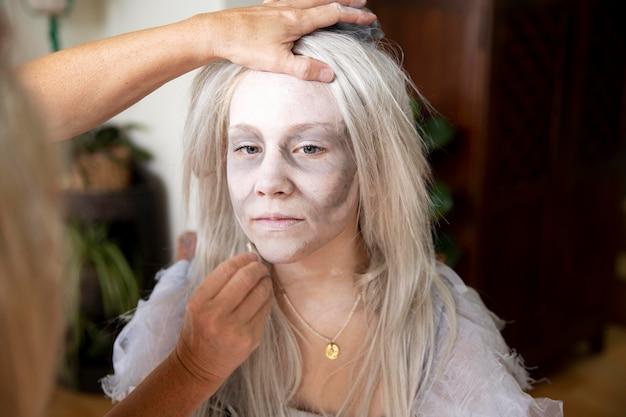 Menina se preparando para o halloween com uma fantasia de fantasma