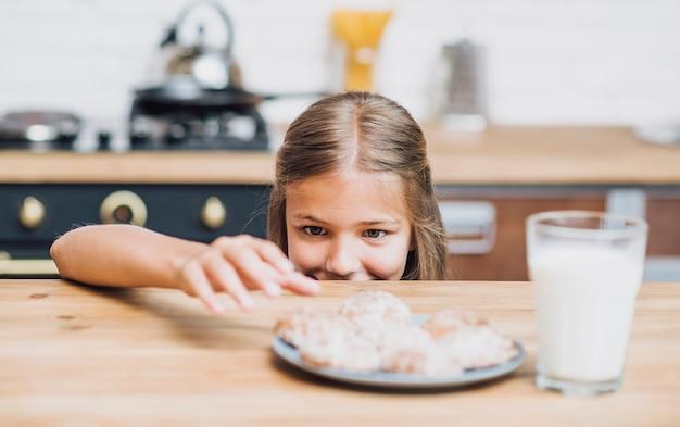 Menina se preparando para tomar um biscoito