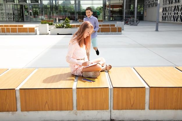 Menina se senta e lê um livro na porta da escola, perto do prédio da escola. estudante adolescente está correndo em direção a ela no fundo