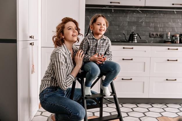 Menina se senta na escada e a mãe dela posa ao lado do contexto da cozinha.