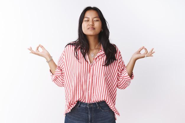 Menina se unindo à meditação da natureza, mostrando o sinal de mudra de lado, fechando os olhos e inspirando ar, praticando ioga na posição de lótus, sentindo-se relaxada e aliviada contra uma parede branca