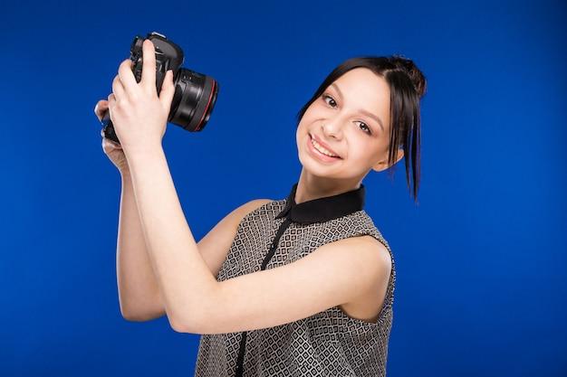 Menina segura a câmera nas mãos