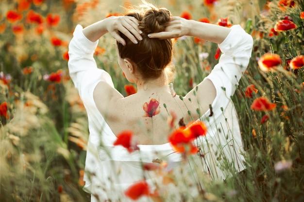 Menina segura as mãos pela cabeça e fica de costas nuas com uma flor de papoula tatuagem, entre o campo de papoulas