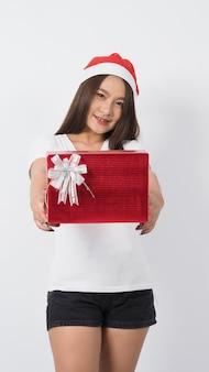 Menina segura caixa de presente fazer selfie ou vídeo online com decoração de adereço de natal de natal. mulher adolescente tailandesa asiática tomando selfie-online para celebrar a época festiva com a amiga pela caixa de presente vermelha. tiro do estúdio.