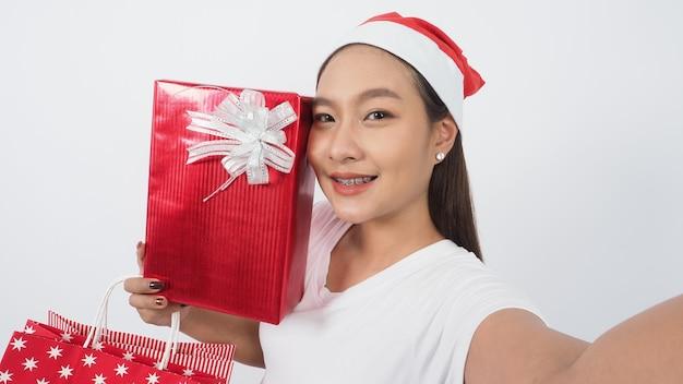 Menina segura caixa de presente para fazer selfie ou vídeo on-line com decoração de adereços de natal de natal. adolescente tailandês asiático
