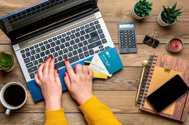 Menina segura cartão de débito, escolhe presentes, faz compras, laptop, xícara de café, dois corações, bolsa de madeira