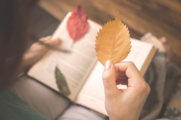 Menina segura folha de outono em fundo de um livro velho. foto de fundo do conceito aconchegante de hygge