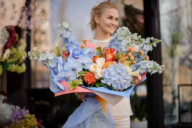 Menina segura grande buquê de flores azuis