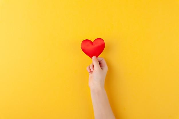 Menina segura nas mãos corações vermelhos, braços de crianças, conceito de amor e dia dos namorados