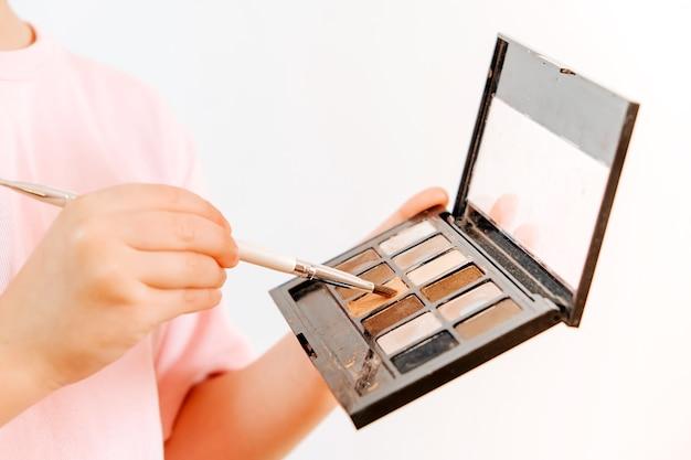 Menina segura paleta com sombras nas mãos. conceito de maquiagem