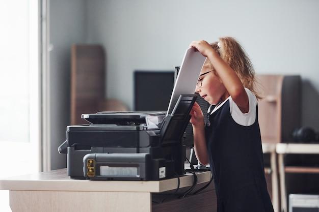 Menina segura papel e coloca na impressora