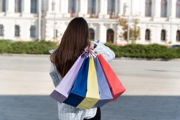 Menina segura sacolas de papel multicoloridas nas costas. vista traseira.