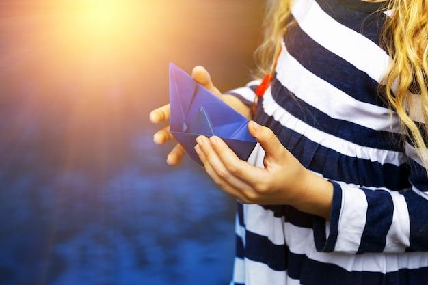 Menina segura um barco de papel azul em uma poça após a chuva, verão