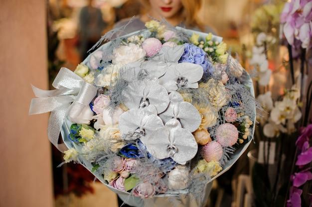 Menina segura um buquê enorme com orquídeas prateadas, hortênsia azul, rosas roxas