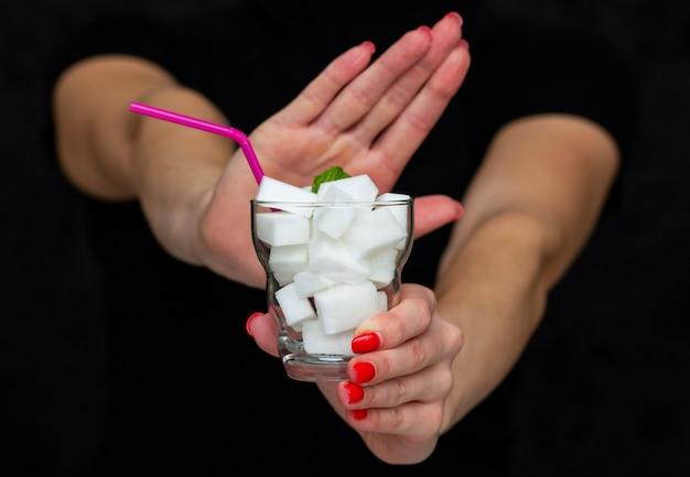 Menina segura um copo cheio de cubos de açúcar branco, rejeita o uso de açúcar