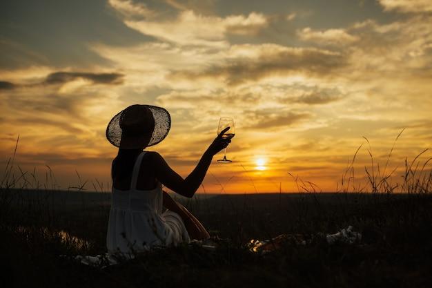Menina segura um copo de vinho com vinho branco na mão na noite de verão do céu do sol.